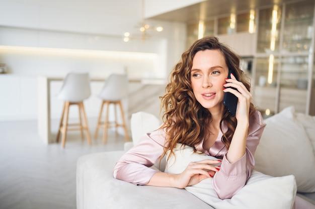 Mooie jonge vrouw met krullend haar in roze pyjama's op witte bank in de ochtend. dame sprekende telefoon in scandinavische stijl woonkamer interieur.