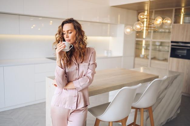 Mooie jonge vrouw met krullend haar koffie drinken in weekend ochtend in gezellige roze pyjama. dame in het moderne binnenland van de skandinavische stijl witte keuken.