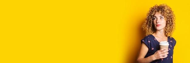 Mooie jonge vrouw met krullend haar met een kartonnen beker op een gele ondergrond
