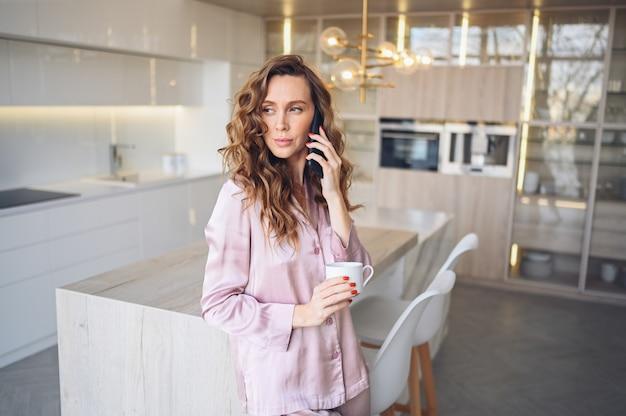 Mooie jonge vrouw met krullend haar thuis koffie drinken in luie weekend ochtend in gezellige roze pyjama.