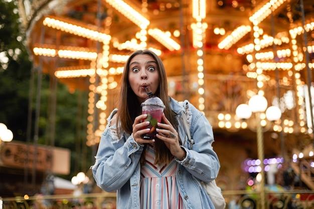 Mooie jonge vrouw met lang bruin haar kijkt met wijd open ogen en samentrekkend voorhoofd, drinkt limonade terwijl ze door park met attracties loopt