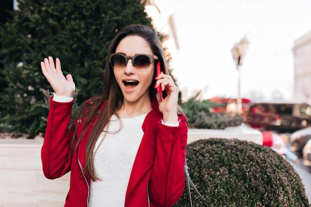 Mooie jonge vrouw met lang bruin haar verwondering uiten tijdens het gesprek aan de telefoon