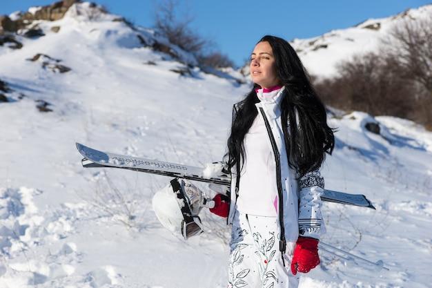 Mooie jonge vrouw met lang donker haar en gesloten ogen staan met ski's en helm als ze in de zon op de berg neemt