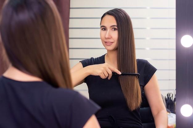 Mooie jonge vrouw met lang, glad bruin haar zorgt voor haar haar. haar haren kammen en in de spiegel kijken