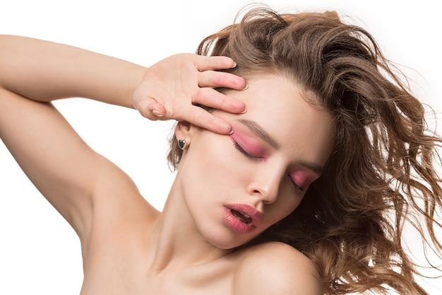 Mooie jonge vrouw met lang golvend zijdeachtig haar, natuurlijke make-up met hand in de buurt van kin geïsoleerd op een witte muur. model met frisse glanzende huid en natuurlijke make-up. emoties van mensen