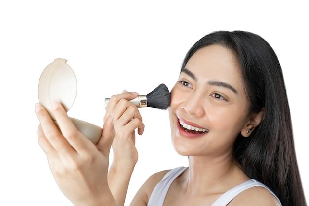 Mooie jonge vrouw met lang haar die make-up toepast met borstel