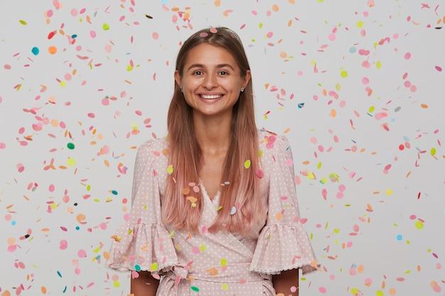 Mooie jonge vrouw met lang haar en geopende mond draagt roze jurk met confetti