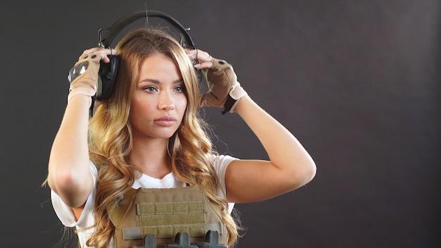 Mooie jonge vrouw met lang haar, gekleed in een militair uniform, poses geïsoleerd tegen een donkere muur met rook op de achtergrond.