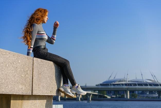 Mooie jonge vrouw met lang haar van blanke nationaliteit in vrijetijdskleding zit aan de kade
