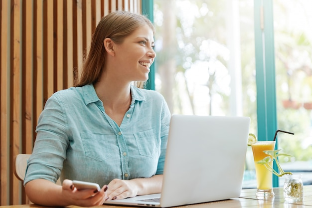 Mooie jonge vrouw met lang haar zittend in café met laptop