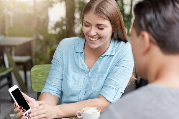 Mooie jonge vrouw met lang haar zittend in café met telefoon en man