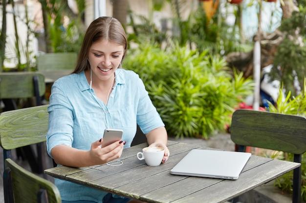 Mooie jonge vrouw met lang haar, zittend in café met telefoon