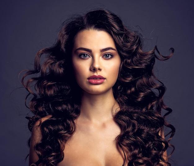 Mooie jonge vrouw met lang krullend bruin haar en rokerige oogmake-up. sexy en schitterend donkerbruin meisje met een golvend kapsel. portret van een aantrekkelijk wijfje. model.