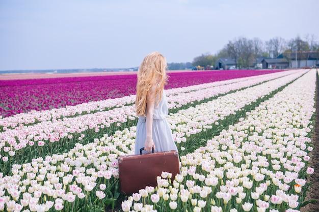 Mooie jonge vrouw met lang rood haar dat in witte kleding draagt die zich met bagage op kleurrijk tulpengebied bevindt.