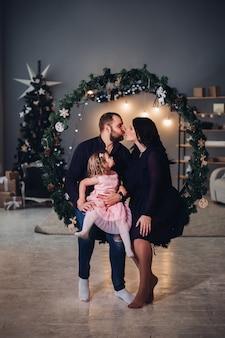 Mooie jonge vrouw met lang zwart golvend haar in jurk, aantrekkelijke sterke man met kort donker haar in shirt en spijkerbroek kersttijd samen met een klein meisje doorbrengen