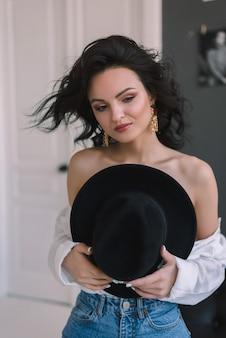 Mooie jonge vrouw met lang zwart haar en zwarte hoed