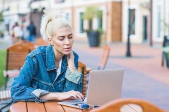 Mooie jonge vrouw met laptop in de open lucht