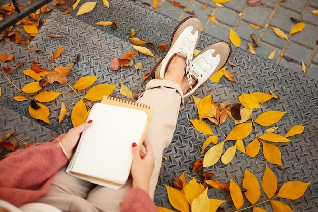 Mooie jonge vrouw met laptop zittend op stappen buiten op herfstdag