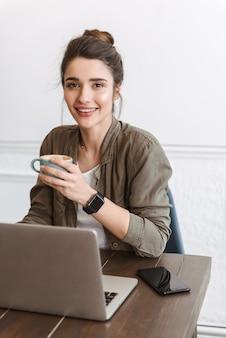 Mooie jonge vrouw met laptopcomputer zittend binnenshuis, koffie drinken