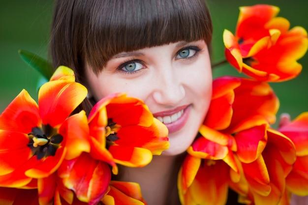 Mooie jonge vrouw met lente tulpen bloemen boeket op city street. gelukkig meisje lacht en houdt rode tulp bloemen buitenshuis. lente portret van mooie vrouw in park.