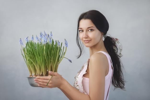 Mooie jonge vrouw met lentebloemen in bloempot kijken naar de voorkant