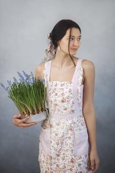 Mooie jonge vrouw met lentebloemen in bloempot