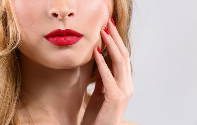 Mooie jonge vrouw met lichte make-up op lichte achtergrond, close-up