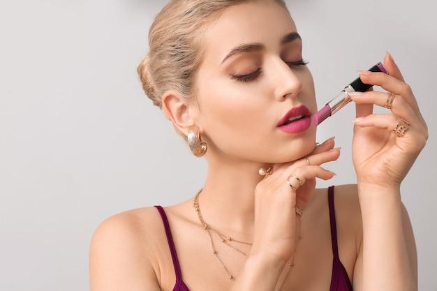 Mooie jonge vrouw met lippenstift op grijze muur