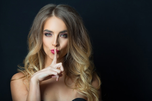 Mooie jonge vrouw met make-up en kapsel met handgebaar