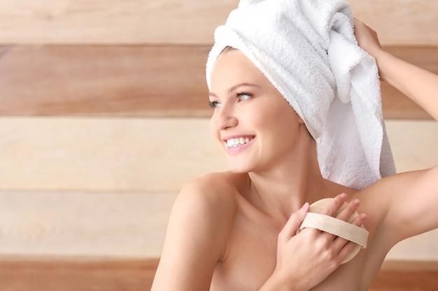 Mooie jonge vrouw met massageborstel op houten