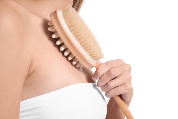 Mooie jonge vrouw met massageborstel op wit, close-up
