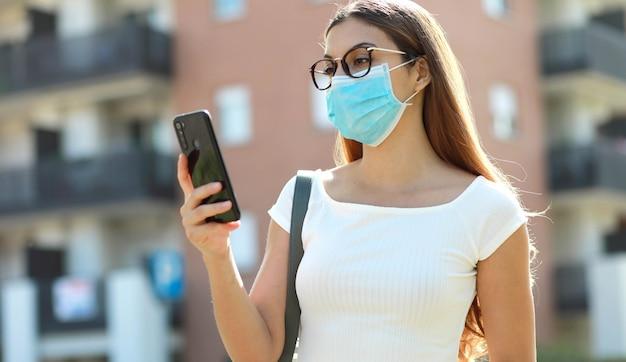 Mooie jonge vrouw met medisch maskeroverseinen op de slimme telefoon in stadsstraat.
