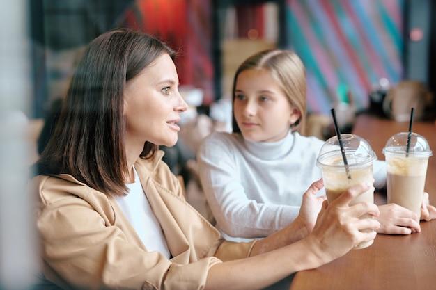 Mooie jonge vrouw met melkcocktail in gesprek met haar schattige dochter terwijl zowel aan tafel in café zit als met drankjes