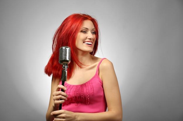 Mooie jonge vrouw met microfoon op grijze ondergrond