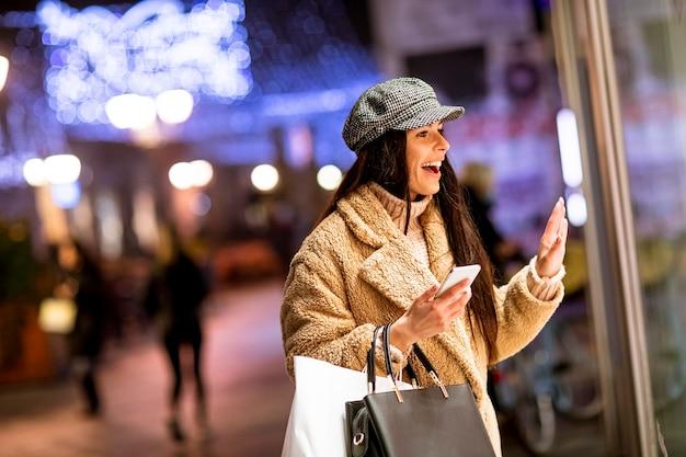 Mooie jonge vrouw met mobiele telefoon bij de etalage in de kersttijd