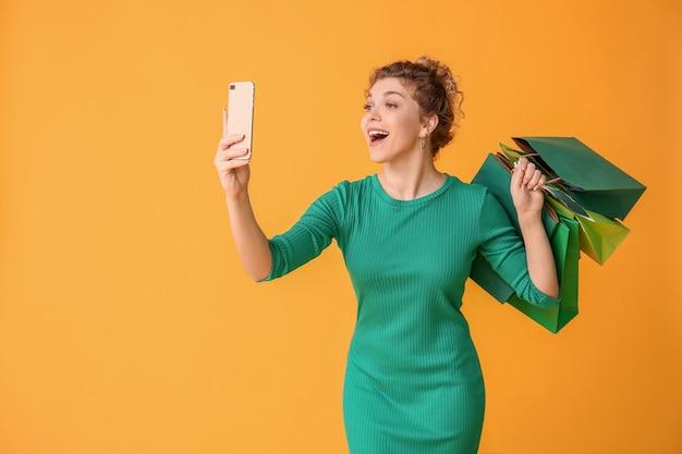 Mooie jonge vrouw met mobiele telefoon en boodschappentassen op kleur