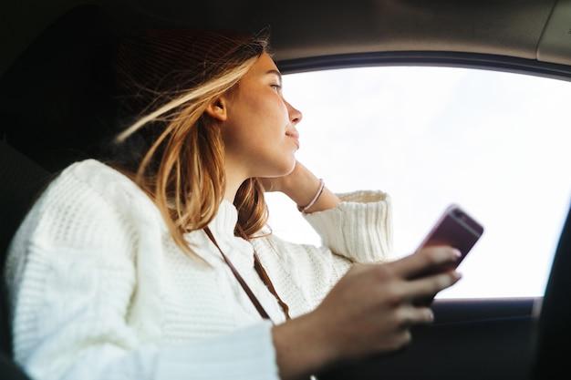 Mooie jonge vrouw met mobiele telefoon zittend in een auto, kijkend naar raam