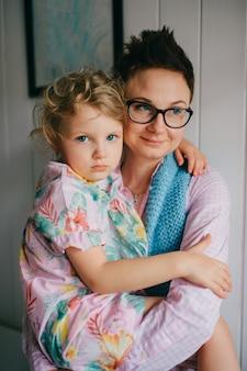 Mooie jonge vrouw met mooi gezicht, kort donker haar, grote ogen houdt haar kind vast en verheugt zich