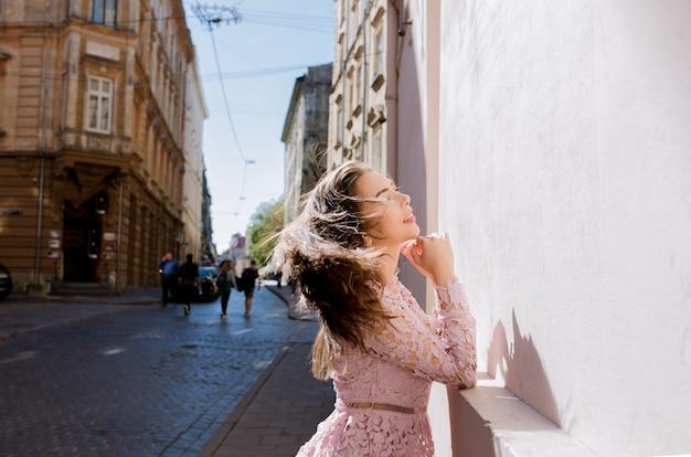 Mooie jonge vrouw met mooi haar in de wind poseren op straat in zonnige dag. vrouw die modieuze kanten jurk draagt