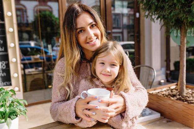 Mooie jonge vrouw met mooie dochtertje gekleed in warme truien op straat