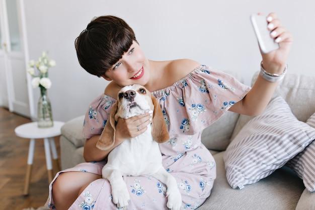 Mooie jonge vrouw met naakte make-up die met liefde haar beaglehond aanraakt en een foto van zichzelf maakt