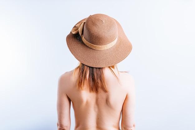 Mooie jonge vrouw met naakte rug in hoed op witte achtergrond met polka dots op huid. zomer huidverzorging concept. zonnebaden. topless