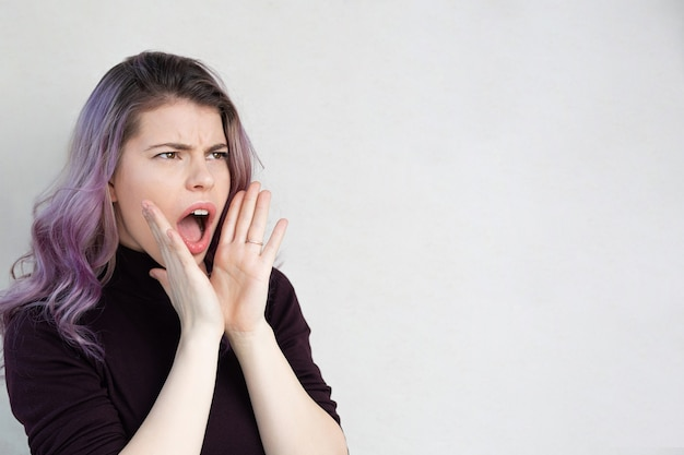 Mooie jonge vrouw met paars haar die schreeuwt en naar de zijkant kijkt. ruimte voor tekst
