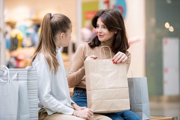 Mooie jonge vrouw met paperbag kijken naar haar dochter tijdens het bespreken van aankoop in paperbag na het winkelen in het winkelcentrum