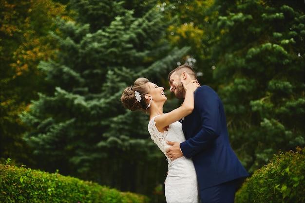 Mooie jonge vrouw met perfect lichaam en huwelijkskapsel in kanten jurk knuffels en zoenen