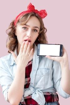 Mooie jonge vrouw met pin-up make-up en kapsel over roze achtergrond met mobiele telefoon