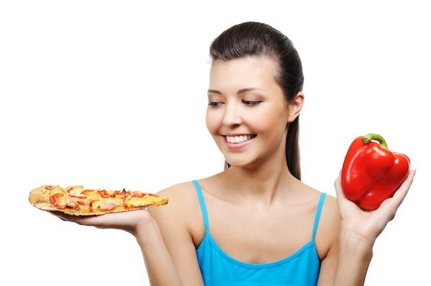 Mooie jonge vrouw met pizza in één hand en spaanse peper in andere