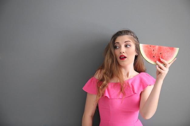 Mooie jonge vrouw met plakje smakelijke watermeloen op grijze achtergrond