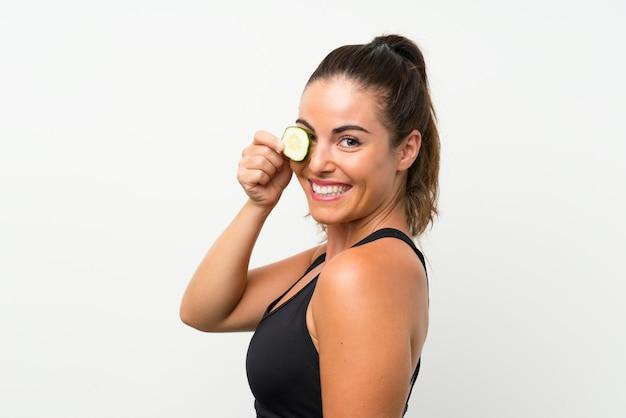 Mooie jonge vrouw met plakjes komkommer