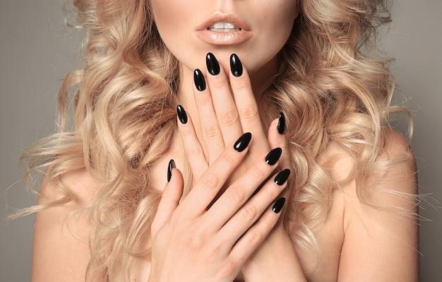 Mooie jonge vrouw met professionele manicure op grijs, close-up